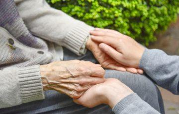 高齢者の手を握る